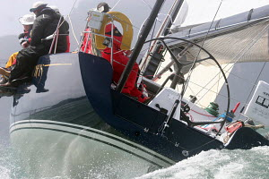 Crew sitting on upside gunwale of yacht competing at the start of the Pacific Cup to Hawaii Race, San Francisco Bay, California. July 17, 2008. - Sandra Cannon