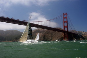 Yacht competing at the start of the Pacific Cup to Hawaii Race, passing under the Golden Gate Bridge, San Francisco Bay, California. July 17, 2008. - Sandra Cannon