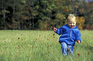 Young boy running through grass meadow, Kennebunkport, Maine, USA  -  Jerry Monkman