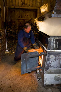 Tending the fire under a sap evaporator in a sugar house in Barrington, New Hampshire, USA. the Sugar Shack, manufacture of maple syrup.  -  Jerry Monkman
