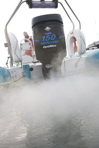 Exhaust fumes from a 150 Mercury Optimax outboard motor aboard a rib. Cowes, December 2008. Model Released. - Simon Wells