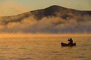Canoeing in Lily Bay iin the mist at sunrise, Moosehead Lake, Maine, USA. Lily Bay Mountian is in the distance. model released  -  Jerry Monkman