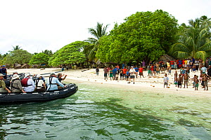 Tourists arrive by zodiac boat and are greeted by locals at Bodaluna Island, Woodlark / Laughlan Islands, Papua New Guinea. (Also known as Budi Budi Island) May 2008 - Michele Westmorland