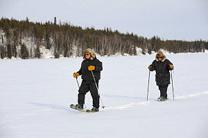 People walking with snowshoes on frozen lake, Yellowknife, Northwest Territories, Canada  -  Eric Baccega