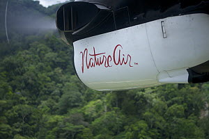'Nature Air' aircraft flying over rainforest. This airline is carbon neutral, offsetting their carbon use by buying rain forest in the Osa Peninsula. Golfito, Puntarenas, Costa Rica.  -  Tim Laman