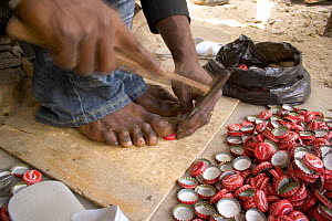 Artisan hammering holes into coke bottle tops, Dakar, Senegal, 2008  -  Tom Gilks