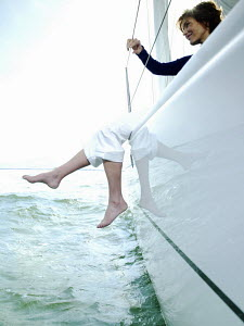 Woman dangling her legs over the side of 40ft yacht sailing on the IJmeer near Amsterdam, Holland. September 2008. - Gary John Norman