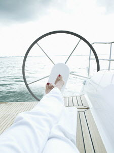 Woman relaxing on 40ft yacht sailing on the IJmeer near Amsterdam, Holland. September 2008. - Gary John Norman