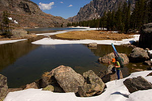 Skier Phil Atkinson passing Elk Lake on the East Rosebud Creek Trail into the Beartooth Mountains, Montana, USA May 2008  -  Tim Laman