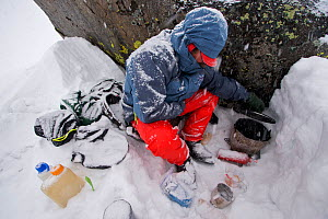 Skier Phil Atkinson cooks dinner in a snow storm at a camp near Sky Top Lakes, on the approach to Granite Peak, Beartooth Mountains, Montana, USA. May 2008  -  Tim Laman