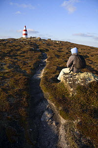 Walker sitting near the Daymark, erected in the 1600s. St.Martin's, Isles of Scilly December 2008.  -  Merryn Thomas