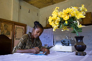 Woman writing out permits to allow visitors into the Daraina forest, where the last Golden Crowned Sifakas (Propithecus tatersalii) live, Daraina, Northeast Madagascar.  -  Inaki Relanzon