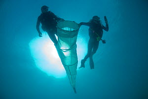 Jo Browne and Kade Mills use a cylinder cone shaped plankton net to sample gelatinous zooplankton for Coral Reef census, Lizard Island, Queensland, Australia, April 2008. Not released. - Jurgen Freund