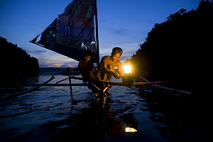 Fisherman and son on traditional sailboat out for night fishing using a kerosine ^Petromax^ lamp to attract fish, Camarines Sur, Luzon, Philippines 2008. - Jurgen Freund