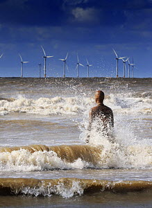 A sculpture of a person in the sea with an offshore windfarm in the distance, Anthony Gormley sculpture Another Place, Crosby, Liverpool, UK, October 2008  -  Graham Eaton