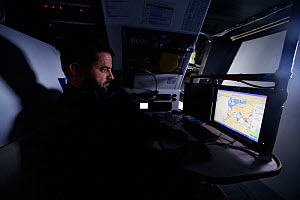 """Skipper Pascal Bidegorry in the navigation room aboard Maxi yacht """"Banque Populaire V"""", practicing off Cadiz, Spain. March 2009.  -  Benoit Stichelbaut"""