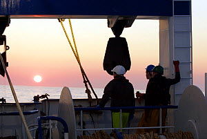 Crewmen watching sunset over the North Sea, from a fishing trawler. September 2008.  -  Philip Stephen
