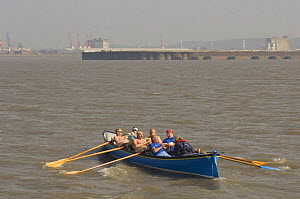 """""""Wolf"""" crew rowers in the Bristol Gig Club """"Bristol Challenge"""" race with Avonmouth and Portbury Docks in the background. March 21st 2009.  -  Rob Cousins"""