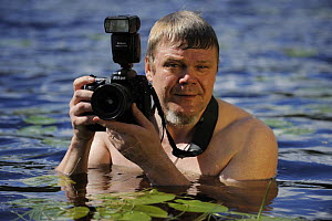 Photographer Lassi Rautiainen holding camera in water, Kuhmo, Finland, July 2008  -  Wild Wonders of Europe / Widstrand