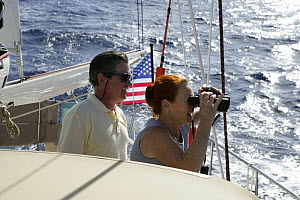 """Couple looking out to sea with binoculars, aboard Amel 54 ketch """"Hollis"""" on delivery from Martinique, Caribbean. 2006.  Model and property released.  -  Billy Black"""