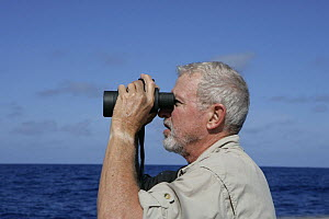 """Man looking out to sea with binoculars, aboard Amel 54 ketch """"Hollis"""" on delivery from Martinique, Caribbean. 2006.  Model and property released.  -  Billy Black"""