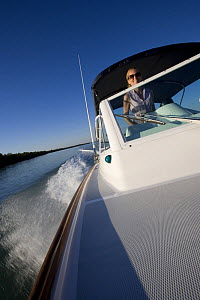 Woman helming Hunt Harrier 25 off Marco Island, Florida, USA. Model and property released, 2007.  -  Billy Black