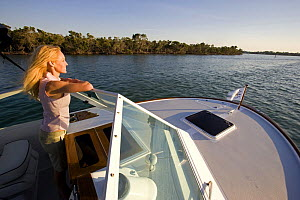 Woman looking over the wind shield aboard Hunt Harrier 25, cruising off Marco Island, Florida, USA. Model and property released, 2007.  -  Billy Black