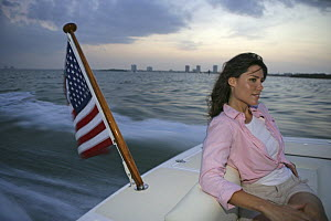 Woman sitting in the stern of a Hunt Harrier 25 off Hollywood, Florida, USA. Model and property released.  -  Billy Black