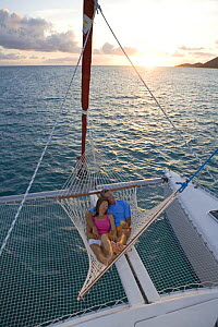 Couple relaxing in hammock on the stern of a Sunsail Lagoon 410 catamaran at sunset. British Virgin Islands, April 2006. Model released and property released.  -  Billy Black
