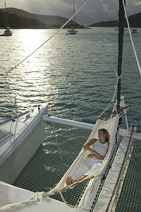 """Woman relaxing in a hammock over trampoline of Lagoon 470 Sunsail charter catamaran """"KooLau"""", British Virgin Islands, January 2004. Model and property released.  -  Billy Black"""