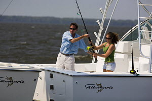 Couple with fishing rod on aftdeck of a sportsfisher.  Model and property released.  -  Billy Black