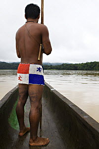Young Embera Indian man heading down the Chagres River, dressed in the traditional beaded skirt (of the Panama flag) Panama, November 2008  -  Piper Mackay