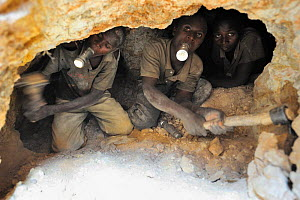 Young men holding their torches in their mouth while digging 10 meters underground in the coltan mines of Muhanga, Rwanda. This mineral is radioactive and these young miners are killing their lungs by...  -  Eric Baccega