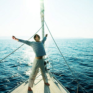 Man with arms outstretched aboard a 46ft sailing yacht, cruising off the Dalmatian Coast in the Adriatic sea, Croatia. July 2006, Model released. - Gary John Norman
