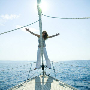 Woman with arms outstretched aboard a 46ft sailing yacht, cruising off the Dalmatian Coast in the Adriatic sea, Croatia. July 2006, Model released. - Gary John Norman