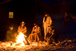 Cowboys sitting round camp fire, Flitner Ranch, Shell, Wyoming, USA Model released - Carol Walker