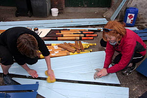 """Two women cleaning the wooden boards of their gig """"Young Bristol"""". Underfall Yard, Bristol, March 2009. - Merryn Thomas"""
