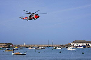 Royal Navy helicopter flying over Cornish Pilot Gig off Town Beach, St. Mary's, Isles of Scilly. World Pilot Gig Championships, May 2009. - Merryn Thomas