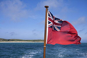 British Merchant Navy ensign on stern of passenger ferry leaving St. Martin's, Isles of Scilly, UK. May 2009.  -  Merryn Thomas