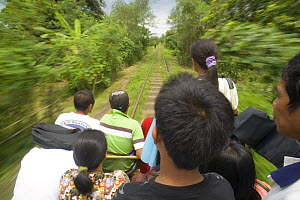 Commuters travelling on a 'skate' - a local form of transport in Manila, Philippines. A motorized platform that can hold up to 30 people and runs on the railway tracks. When the skate meets another he...  -  Jurgen Freund