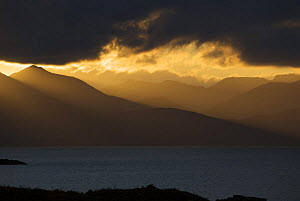 Stormy sunset over mountains on the Isle of Skye seen from the mainland, Scotland, UK. January 2008. - Tim Martin