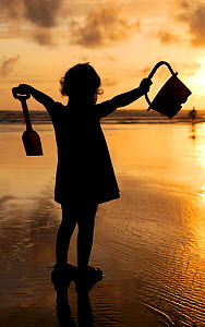 Little girl with bucket and spade silhouetted against setting sun on Summerleaze beach, Bude, North Cornwall, UK. July 2009, Model released.  -  Ross Hoddinott