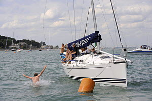"""Man swinging from a rope and jumping into the sea off """"Turbulence II"""", Cowes Week, August 2009. - Rick Tomlinson"""