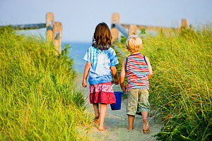 A young brother and sister walking towards the beach at Center Hill Preserve beach, Plymouth, Massachusetts, USA. Model Released. May 2008  -  Jerry Monkman