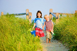 A young brother and sister walking back from the beach at Center Hill Preserve beach, Plymouth, Massachusetts, USA. Model Released. May 2008 - Jerry Monkman