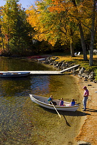 Man launches his three daughters in a rowing boat at Oliver Lodge, Lake Winnipesauke, Meredith, New Hampshire, USA. Model Released. October 2007  -  Jerry Monkman
