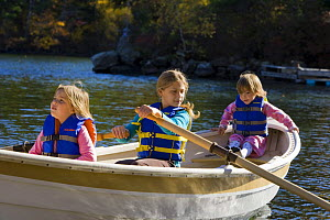 Three young girls (ages 3, 5, 9) in a rowing boat at Oliver Lodge, Lake Winnipesauke, Meredith, New Hampshire, USA. Model Released. July 2008  -  Jerry Monkman