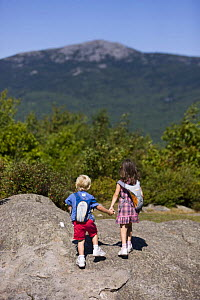 A young brother and sister holding hands while hiking on Gap Mountain, Troy, New Hampshire, USA. Mount Monadnock is in the distance. Model Released. August 2008  -  Jerry Monkman