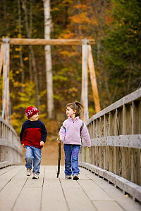 Two children (ages 4 and 6) walking across a wooden suspension bridge, Lincoln's Woods Trail, White Mountains National Forest, New Hampshire, USA. Model Released. October 2007  -  Jerry Monkman