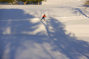 Looking down on a man cross-country skiing (track skiing) on a groomed trail next to the frozen Ottauquechee River in Quechee, Vermont, USA. Model Released.  -  Jerry Monkman